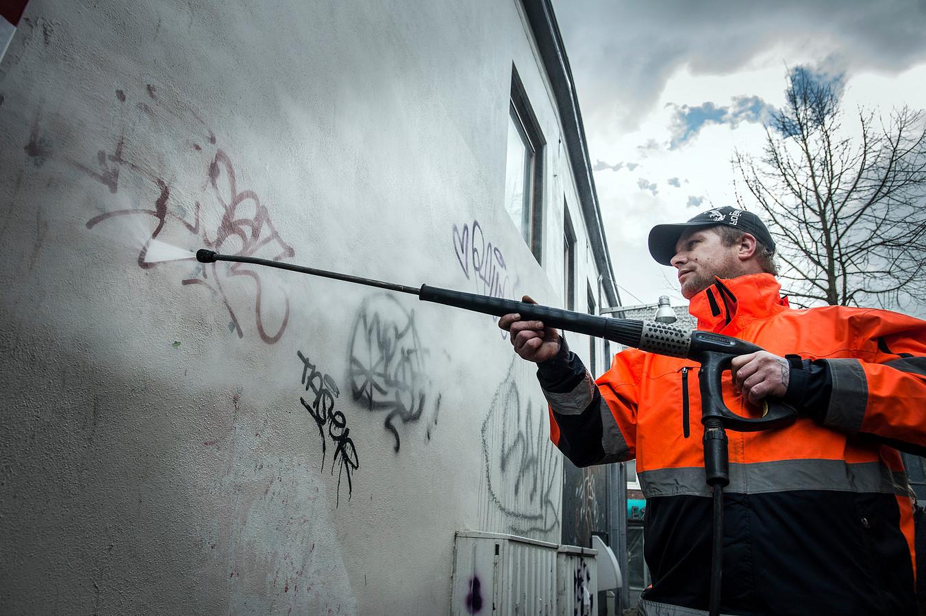 Een medewerker van de Atea-groep is bezig met het verwijderen van graffiti in de Stallingstraat.