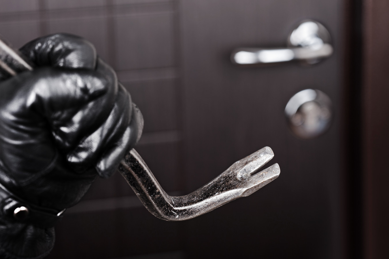 stockadr inbraak inbreker Crime scene - thief or burglar hand in gloves holding metal crowbar break opening home door lock