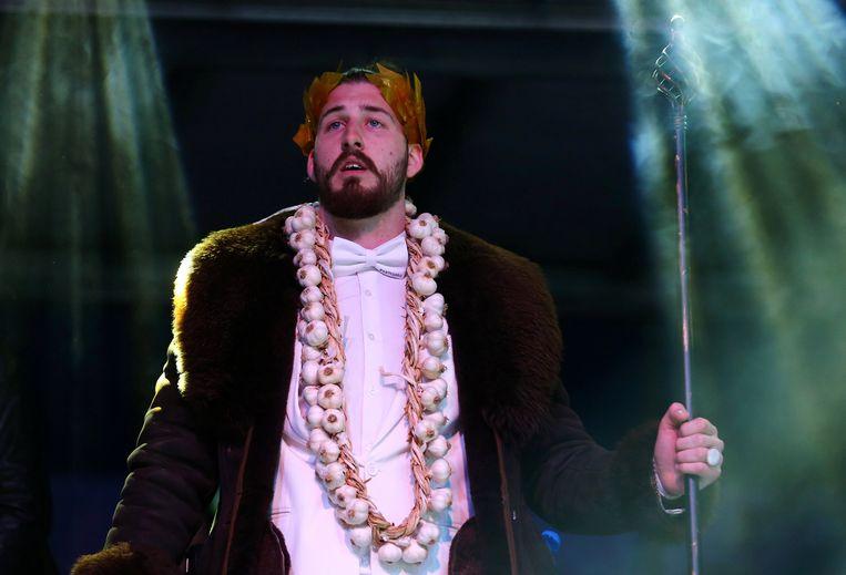 Beli spreekt tijdens zijn campagnebijeenkomst in Mladenovac, getooid met een lauwerkrans en knoflookslinger en met een staf in de hand.