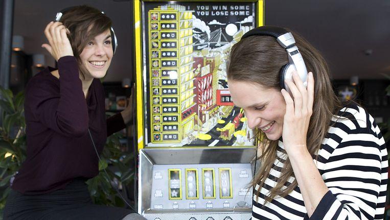 Bieke Versloot (links) en Lieke van Pruijssen testen het geluid van hun fruitautomaat met verhalen. Beeld Io Cooman / de Volkskrant