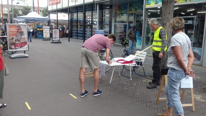 Hans Brouwer zamelt handtekeningen in bij de weekmarkt in Zeewolde tegen de komst van een zonnepark in het Horsterwold.