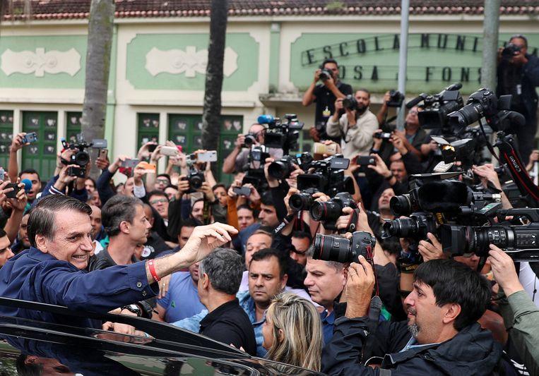 Jair Bolsonaro (links) vlak nadat hij zijn stem heeft uitgebracht. Beeld Reuters