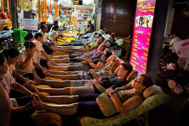 Traditionele Thaise voetmassage op de toeristische Khao San Road, in Bangkok. Beeld Corbis via Getty Images