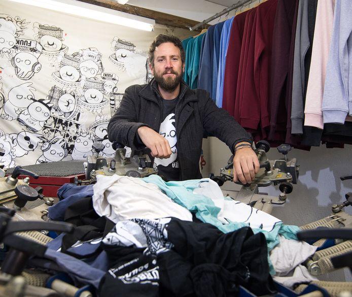 Willem Scholten tussen T-shirts die hij heeft bedrukt met het stripfiguurtje Fuuki.
