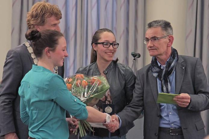 Wethouder Peter Raaijmakers (rechts) feliciteert Imke Ploegmakers (links) en Jinte van der Heijden (midden) van het voltigeteam van De Wittegheit uit Odiliapeel. Linksachter kijkt burgemeester Marnix Bakermans toe.