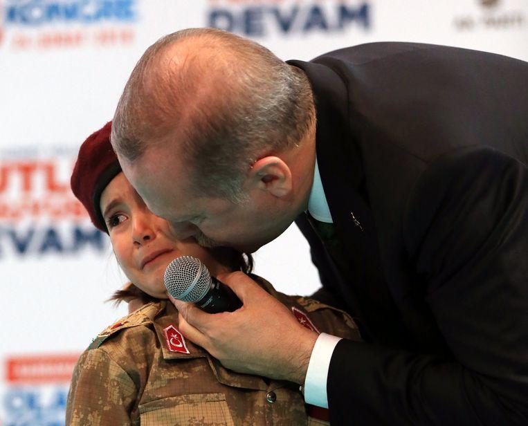 President Erdogan kust een meisje in uniform nadat hij haar bij een congres van de AK-partij op het podium heeft gehaald. Beeld anp