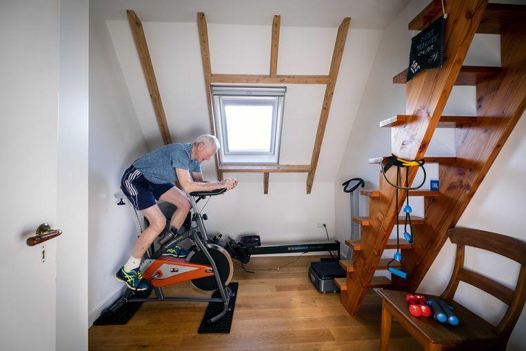 Een oudere man sport in zijn zolderkamer nu de sportscholen gesloten zijn. Beeld ANP