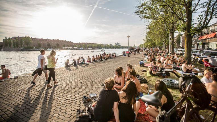 De Weesperzijde is sinds een paar jaar op zomerse dagen een hotspot voor recreërende Amsterdammers. Beeld Eva Plevier