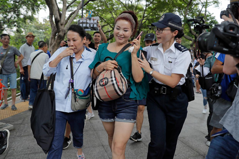 Een straatartieste wordt in veiligheid gebracht tijdens een van de demonstraties in het park van Tuen Mun.