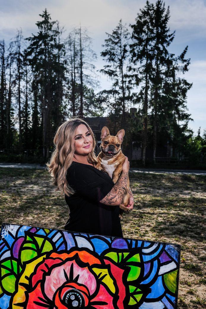 Sharon Elfring met een eigen schilderij en hond Budda.