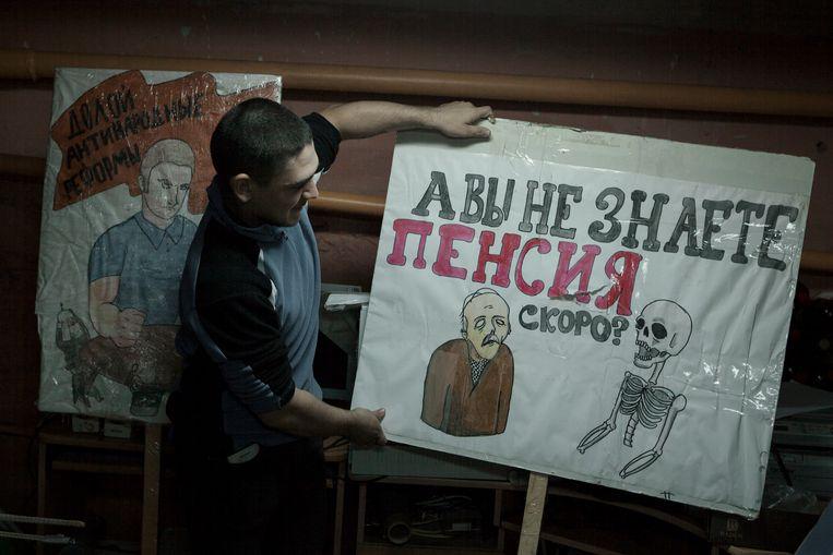 Kirill Starostin laat een poster zien die hij heeft getekend voor een demonstratie tegen het pensioenplan van Poetin, in het hoofdkantoor van de marxistische groep CCCP, in Perm.  Beeld Emile Ducke