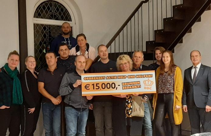 Leden van de Oranjecommissie Brummen bieden de gedupeerden van de grote brand aan het Marktplein in Brummen een cheque van 15 duizend euro aan