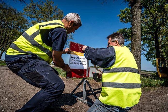 Gemeentemedewerkers plaatsen borden nabij een door het coronavirus getroffen nertsenfokkerij in Nederland.