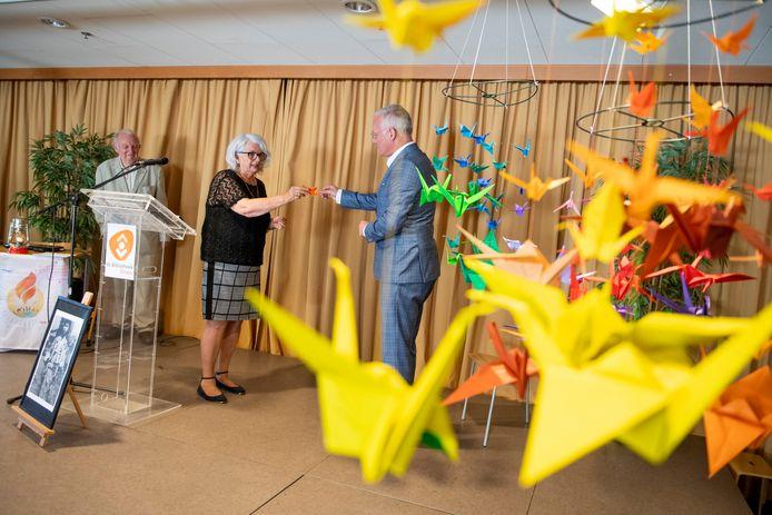 Tegen het decor van een zwerm papieren kraanvogels krijgt burgemeester Arjen Gerritsen uit handen van Cobi Noordhoff een eigen exemplaar van dit symbool tegen kernwapens. Links spreker Ab Gietelink (93).