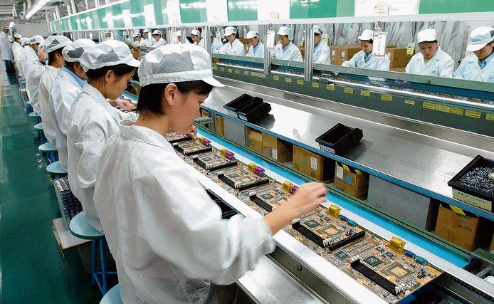 Chinese werknemers in Shenzhen in China monteren chips op een printplaat.