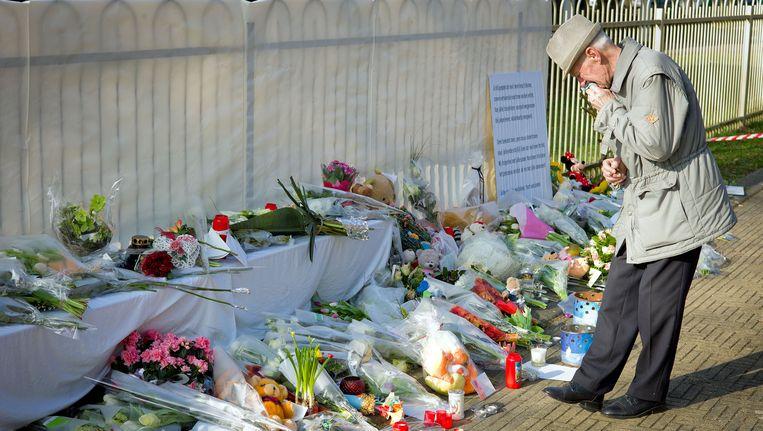 Een man rouwt bij de bloemen die zijn neergelegd ter nagedachtenis aan de slachtoffers van het busongeluk Beeld anp