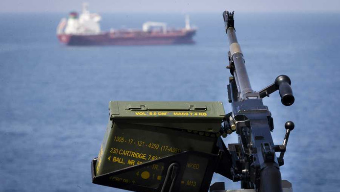 Militairen varen langszij een vrachtschip om het te beschermen tegen piraterij.