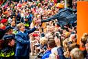 Koning Willem-Alexander tijdens Koningsdag 2018 in Groningen. Geschaduwd door de politie schudt hij de handen van het publiek.