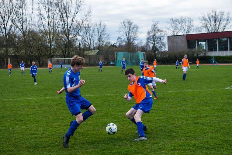 Twee jonge voetballert strijden om de bal.