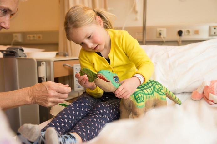 Een van de patiëntjes in ziekenhuis St Jansdal in Harderwijk speelt met een interactieve dinosaurus.