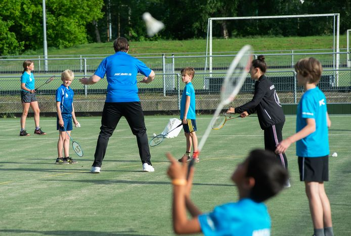 De Heesche badmintonclub HBV mag niet binnen sporten tot september. Toto die tijd trainen ze buiten. Op de foto trainer Hennie Bruurmijn die uitleg geeft.