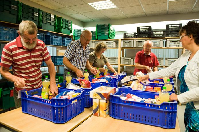 Vrijwilligers van de Voedselbank Hardenberg Ommen druk met pakketten vullen. (archieffoto)