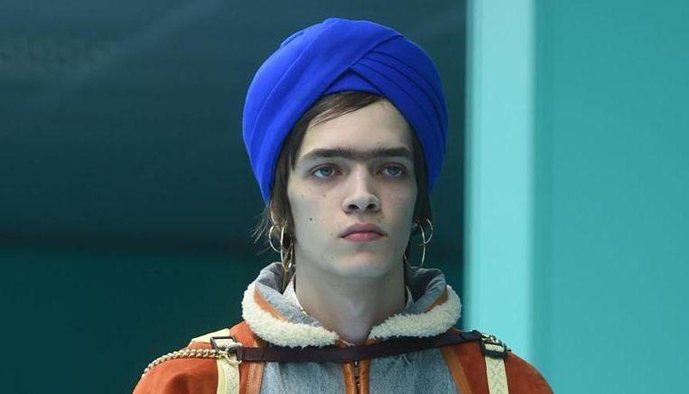 Een model toont de tulband van Gucci voor het eerst tijdens de modeshow in Milaan.