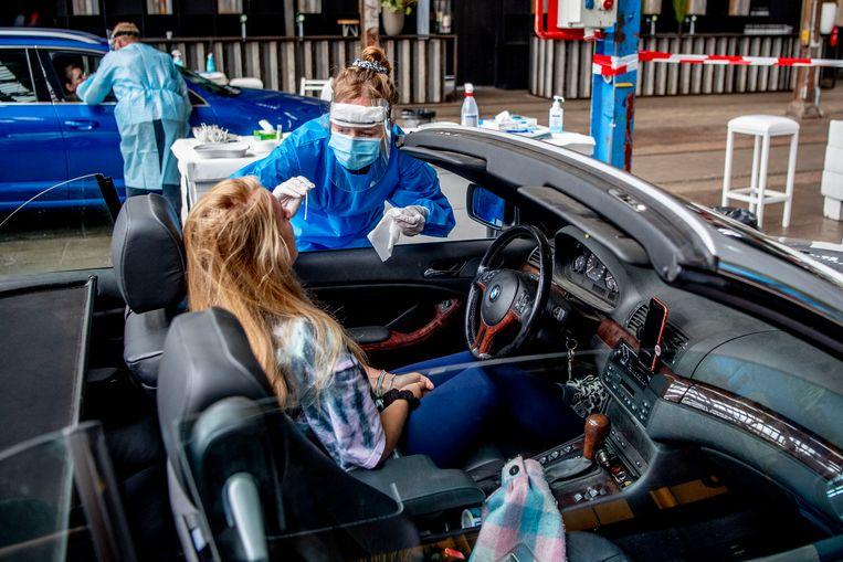 Een medewerker van de GGD neemt een coronatest af in een teststraat in Amersfoort. Beeld Getty