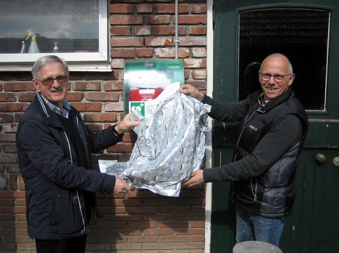 Henk Vermeer (rechts) verricht de onthulling van het nieuwe AED-apparaat samen met Sjef van Iersel.