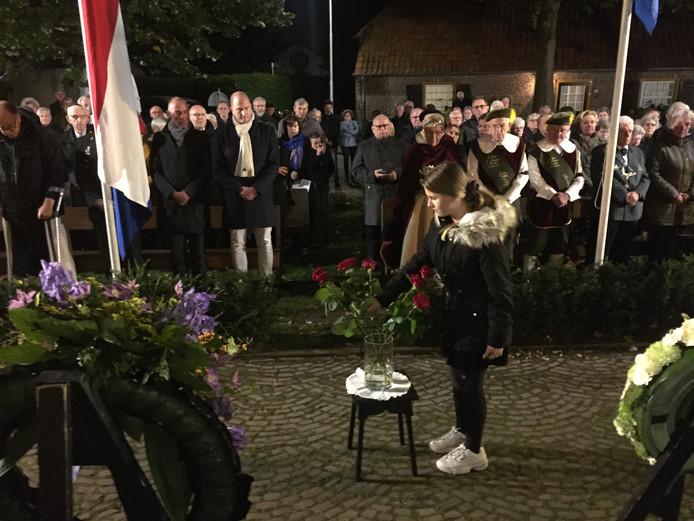 Vijftien kinderen leggen elk een roos ter nagedachtenis aan de vijftien inwoners van Berkel-Enschot die omkwamen door oorlogsgeweld.
