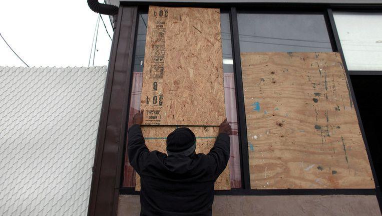 Een inwoner van Queens barricadeert zijn huis.