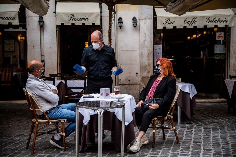 De eerste klanten op Piazza Capranica op 18 mei Beeld Photo News