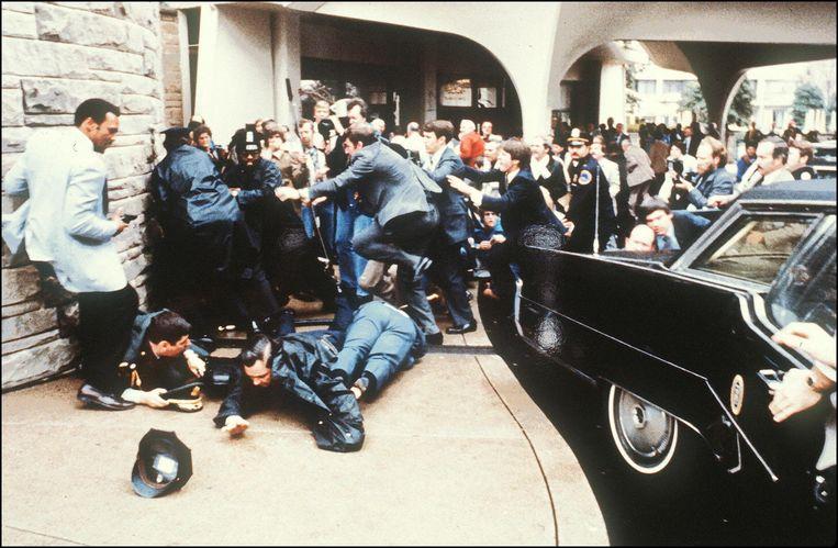 Agenten van de Secret Service, sommige met uzi-machinepistolen, in actie tijdens de mislukte moordaanslag in 1981 op president Ronald Reagan. Beeld AFP