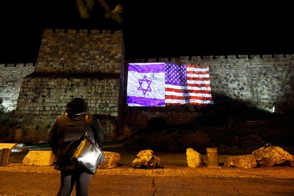 Een vrouw kijkt naar de projectie van de Amerikaanse en Israëlische vlag op de muur van de Oude Stad in Jeruzalem.