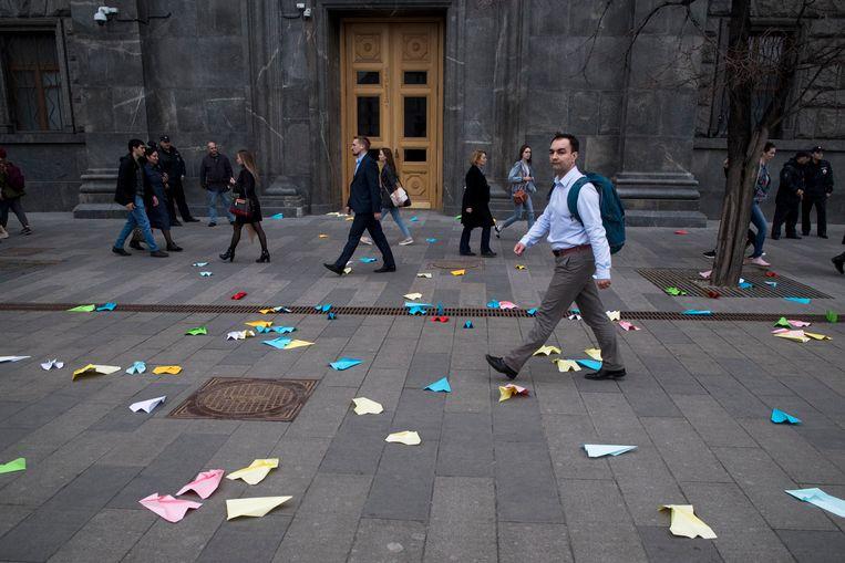 Mensen lopen langs papieren vliegtuigjes - het symbool van Telegram - die zijn rondgestrooid op het plein waar ook de veiligheidsdienst FSB zit. Beeld null