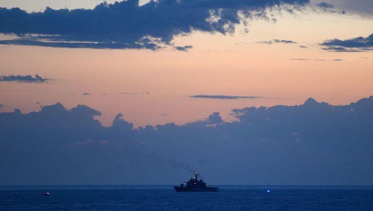 Een millitair schip voor de kust van Lampedusa waar ook gisteren nog tientallen lichamen werden geborgen. Beeld afp
