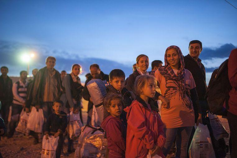 Vluchtelingen en asielzoekers staan in de rij voor een registratiekamp aan de Grieks-Macedonische grens.