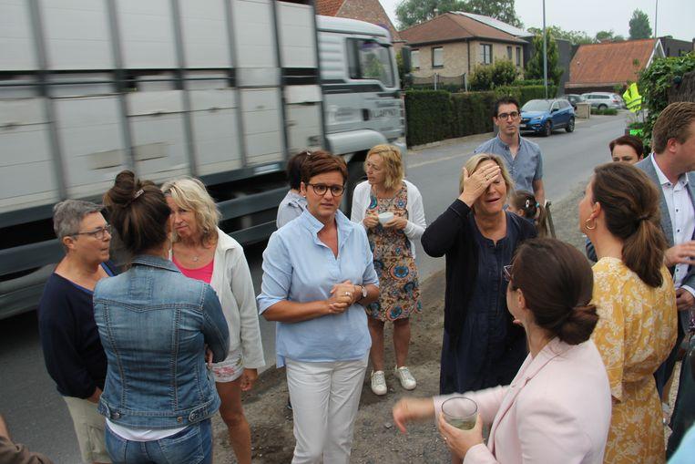 Vrachtwagens denderen voorbij op het moment dat schepenen Caroline Maertens, Ann Van Essche en burgemeester Bert Maertens de inwoners toespreken.