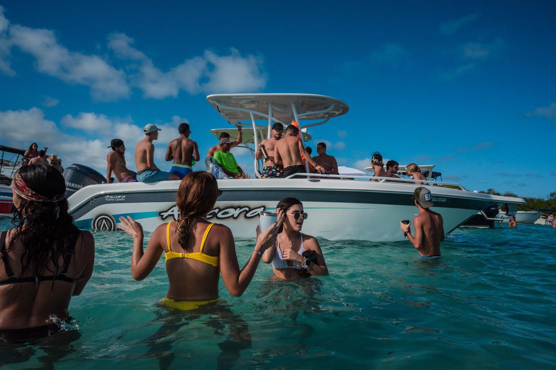 Venezolanen amuseren zich in het water van de Caribische Zee. Alleen de bovenlaag, die beschikt over Amerikaanse dollars, kan uitbundig feestvieren.