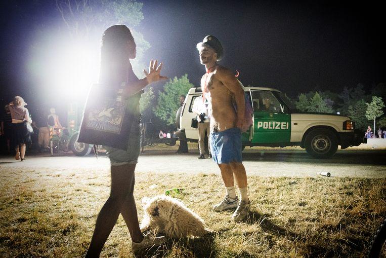 Een man met een snor begint vol overgave te strippen voor een van de politiebussen. 'Come on, you don't wanna be that guy!', roept zijn vriendin.  Beeld Daniel Rosenthal / de Volkskrant