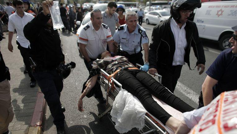 Ambulancepersoneel met een gewonde Palestijnse vrouw. Ze werd door de politie neergeschoten nadat ze een agent met een mes aanviel. Beeld afp