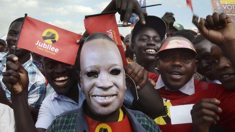 Supporters van de Keniaanse president Kenyatta. Midden een man met een masker van het gezicht van Kenyatta. Beeld AFP