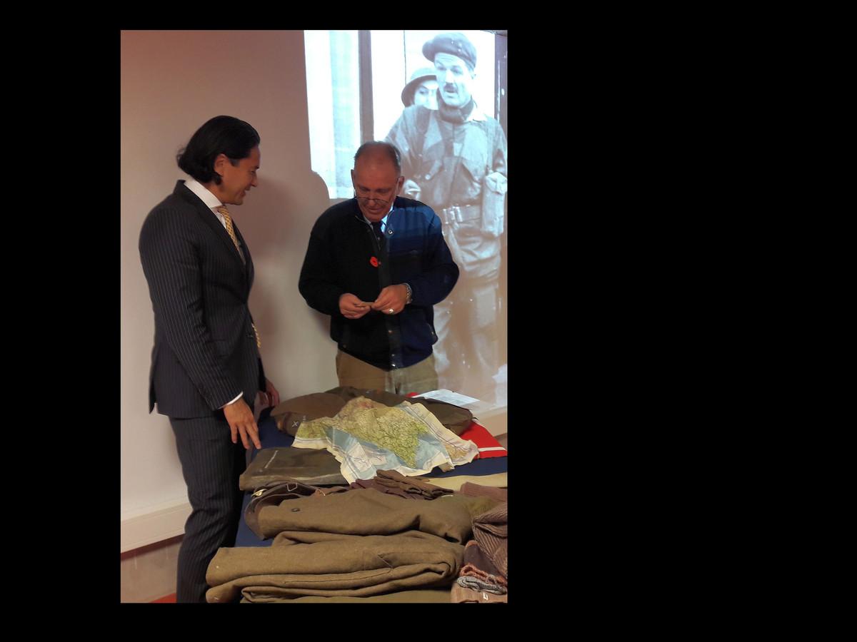 Burgemeester Harald Bergmann (links) en Gert-Jan de Rooij bij de uitrusting van John Knox, wiens foto op de achtergrond is geprojecteerd.