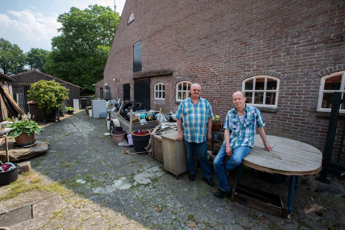 Huurders Jan van de Vijver (l) en Wim Vaes bij de boerderij die ze huren van een Deurnese nertsenhouder.