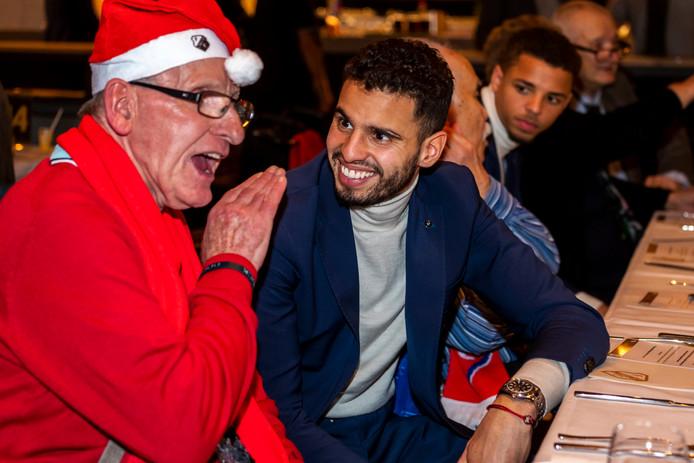 Het kerstdiner van FC Utrecht voor ruim 200 eenzame ouderen uit de provincie. FC Utrecht-middenvelder Adam Maher (rechts) en Kees Ruitenberg genieten van elkaars verhalen.