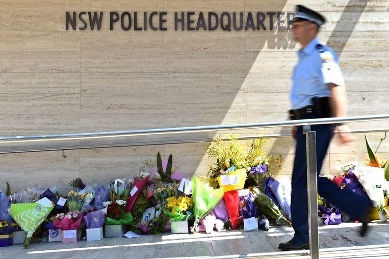 Een agent loopt voorbije bloemen die werden neergelegd aan het hoofdkwartier van de politie in Sydney voor de doodgeschoten agent Curtis Cheng.