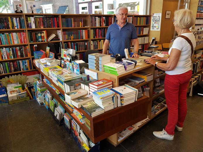 Ad Goos helpt een klant in zijn boekwinkel.