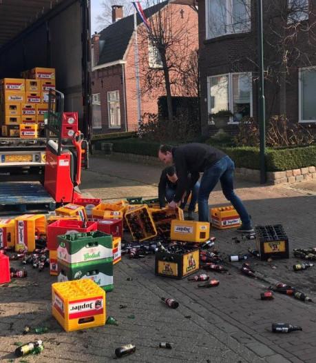 Ongelukkige chauffeur laat stapel vol bierkratten op straat vallen