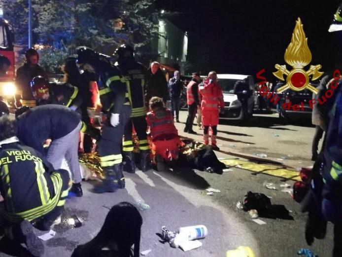 Brandweer en ambulancepersoneel verlenen eerste hulp voor de discotheek.