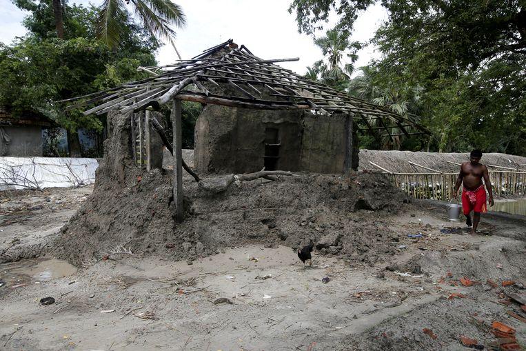 Een man wandelt voorbij een huis dat verwoest werd door het water.